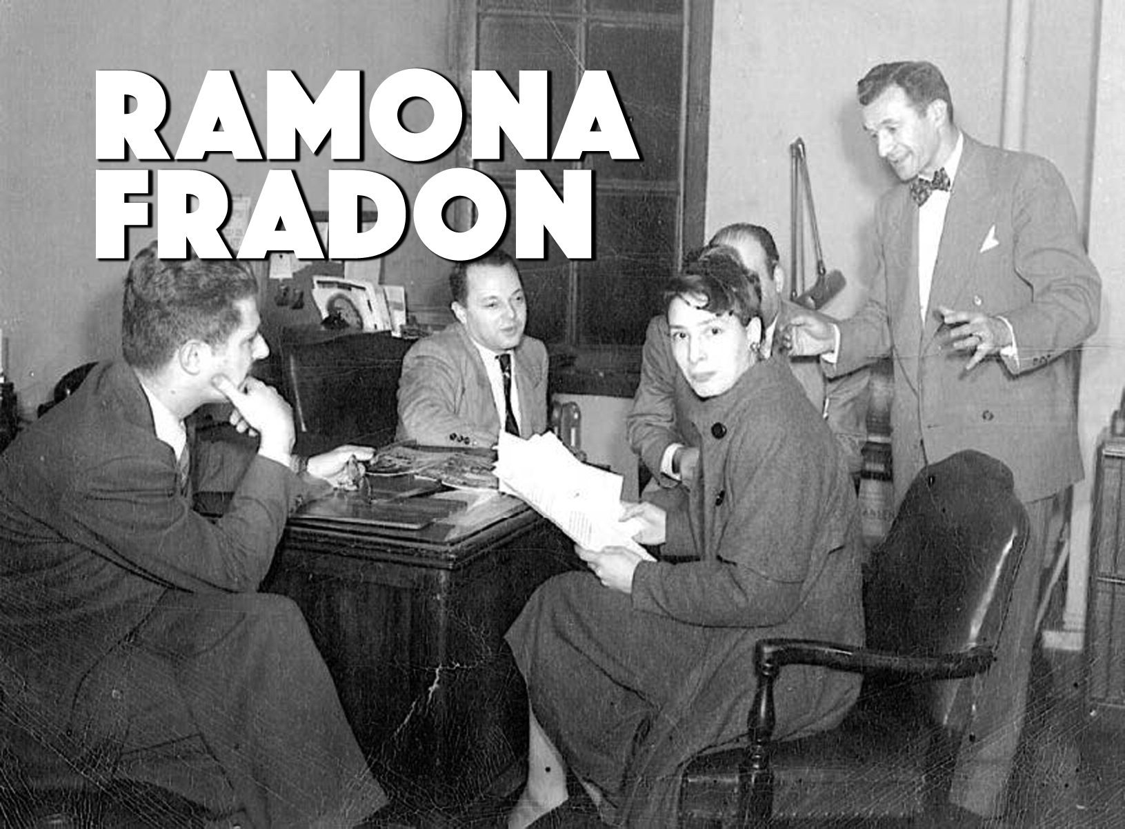 Ramona Fradon sitting in a bullpen, surrounded by male co-workers.