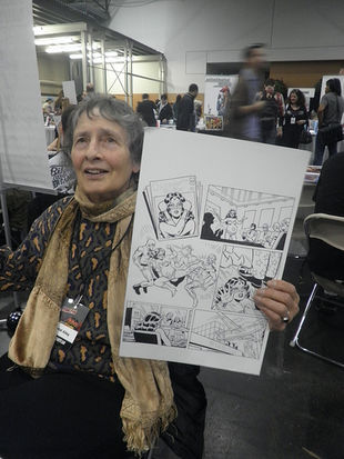 Ramona Fradon holding a page of her original art.