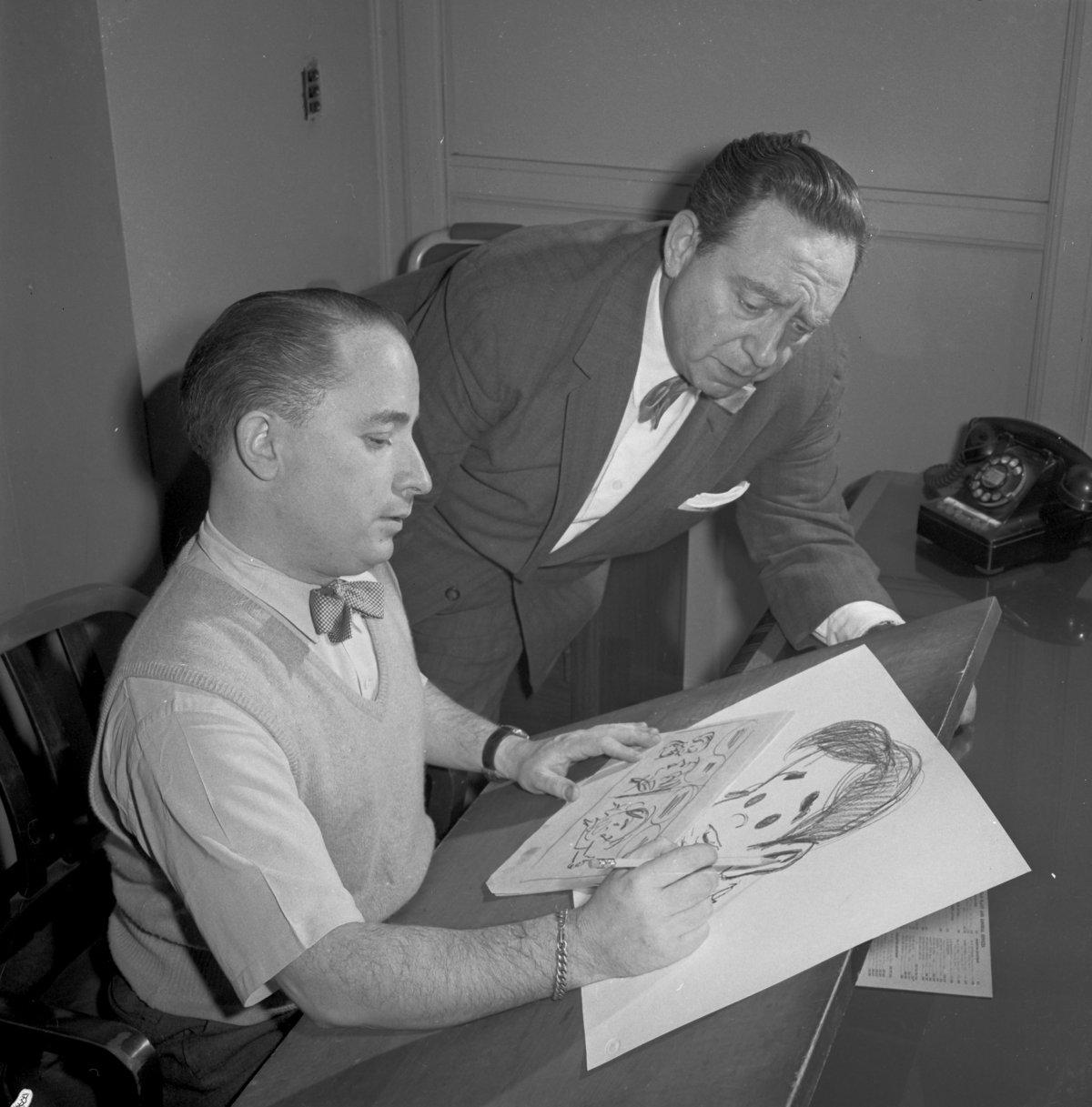 Irwin Hasen (seated at his drawing table) and Gus Edson (standing) discuss Dondi.