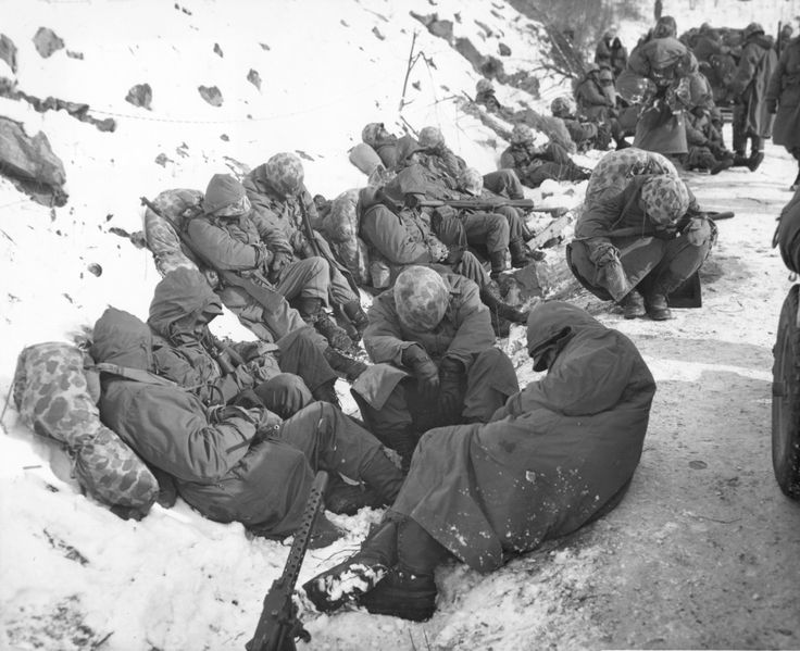 Leathernecks from the 7th Marine Regiment are able to catch a few moments rest during their heroic breakout from the Chosin Reservoir on December 6, 1950.