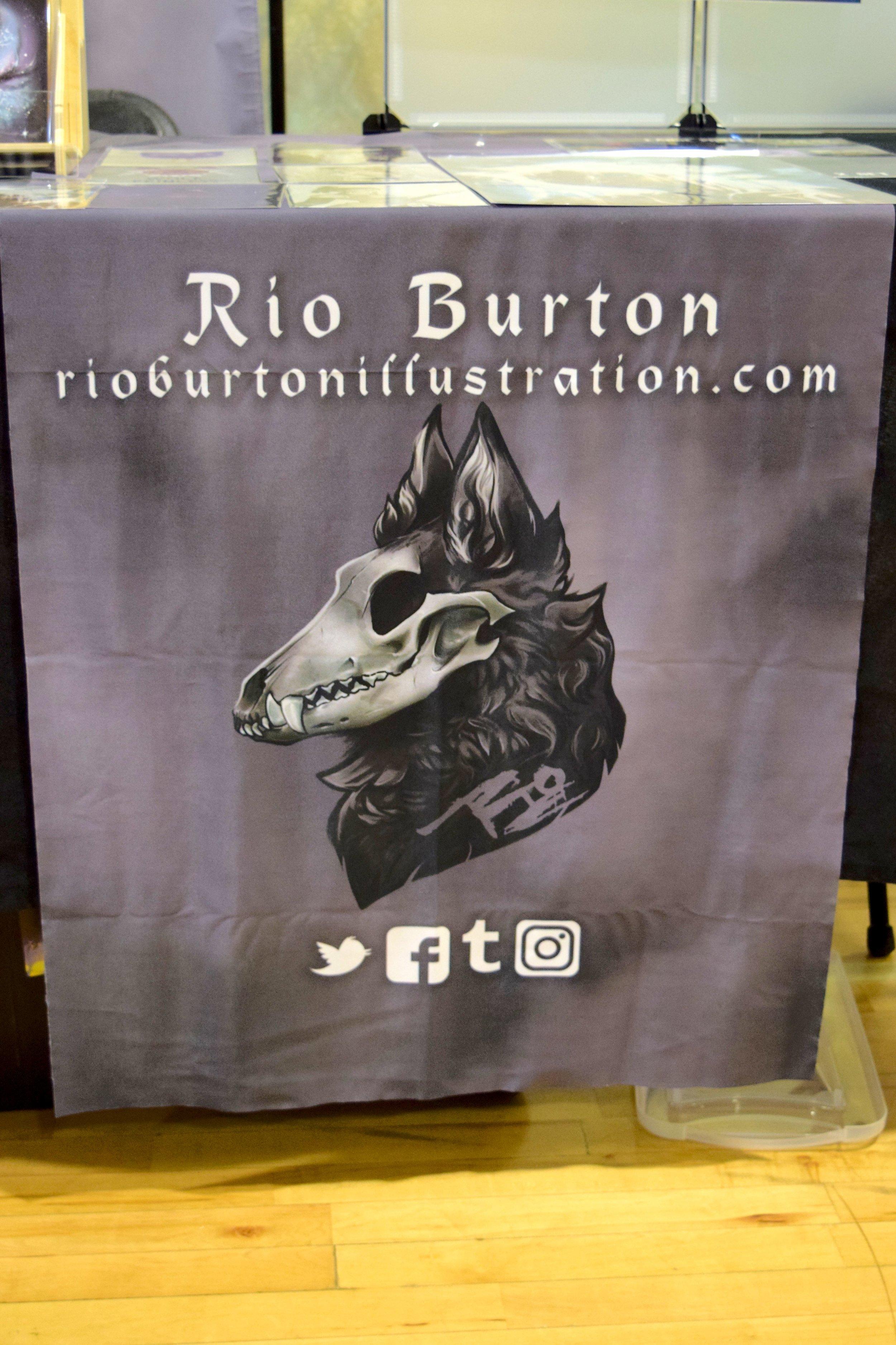 Rio Burton's table banner at Fort Collins Comic Con 2018.