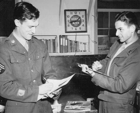 Hugh Hefner (on the left) stands in full military uniform with Hy Eisman sketching (on the right).