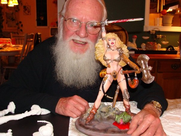 Frank Thorne posing with a Red Sonja statue.