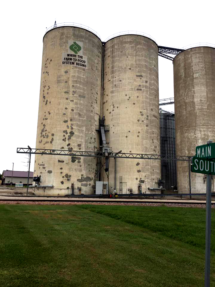 The immensity of the storage elevators always makes me wonder WHO does buy all those corn and beans. Do we really feed the world? Dave is the spec with red and yellow bike panniers waving at the camera as he stands near the base between the first two giants.