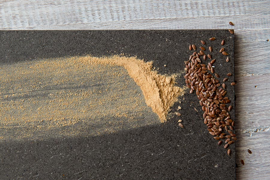 A close-up of maca powder and flaxseeds