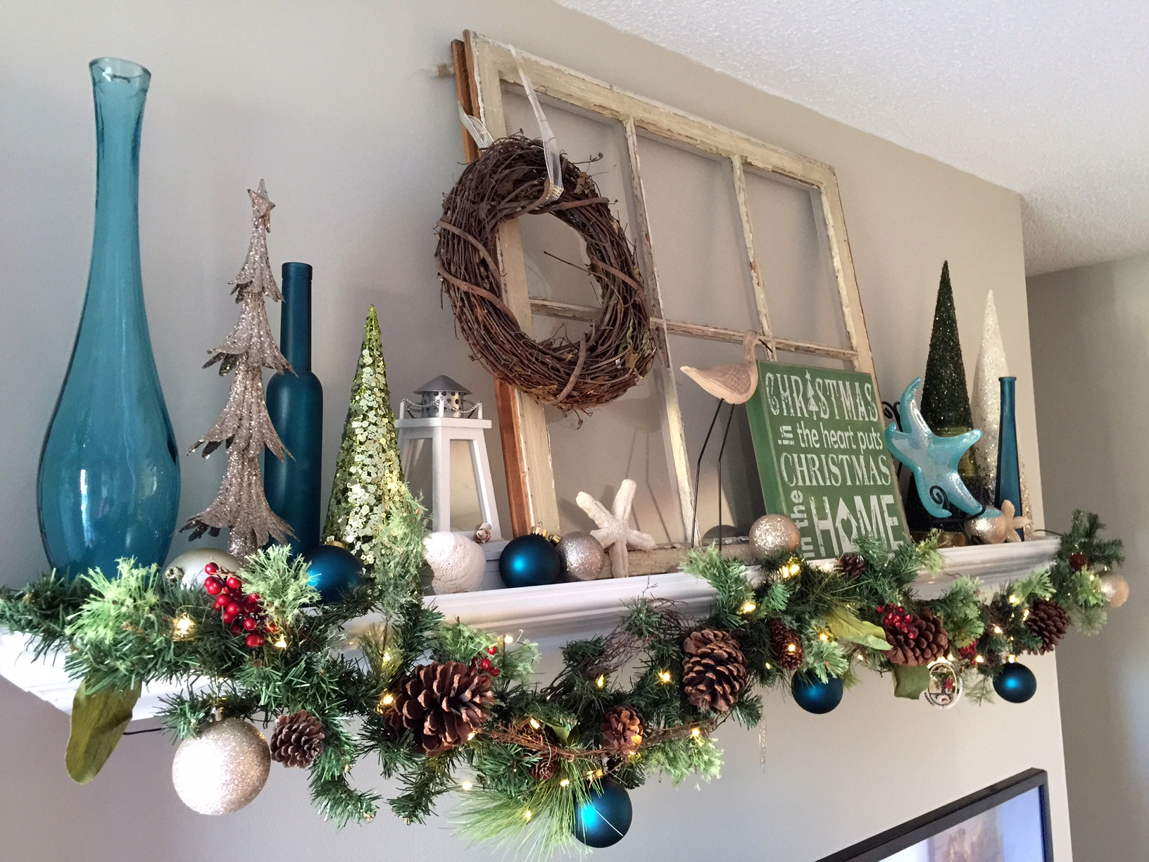 My 2015 Holiday Mantle - Decorative holiday garland with mini lights, teal and champagne colored ornaments in addition to DIY salt dough starfish for a seaside inspired holiday decor.