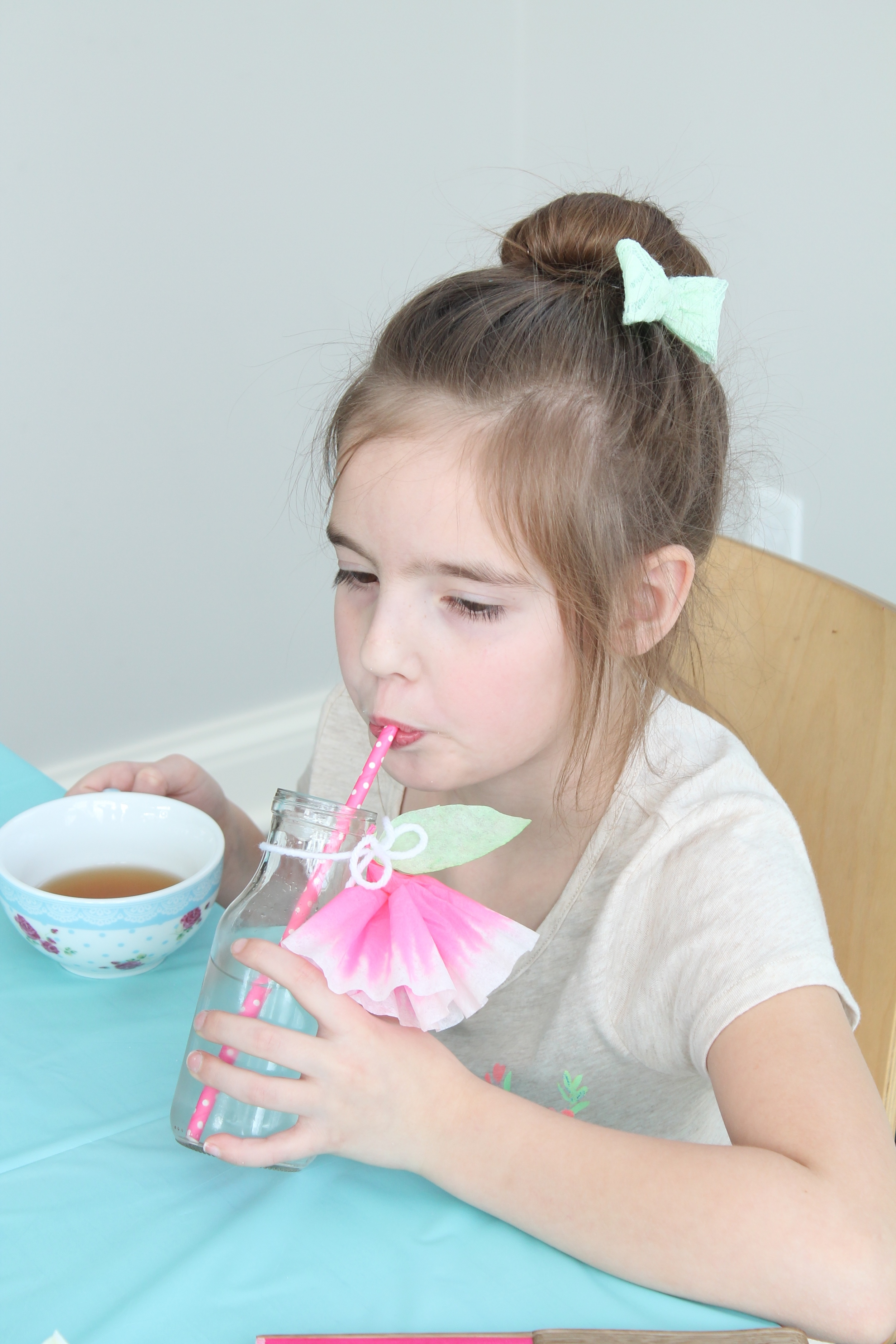 Simple coffee filter flowers tied around a glass milk bottle with string. The perfect drink for a garden tea party.