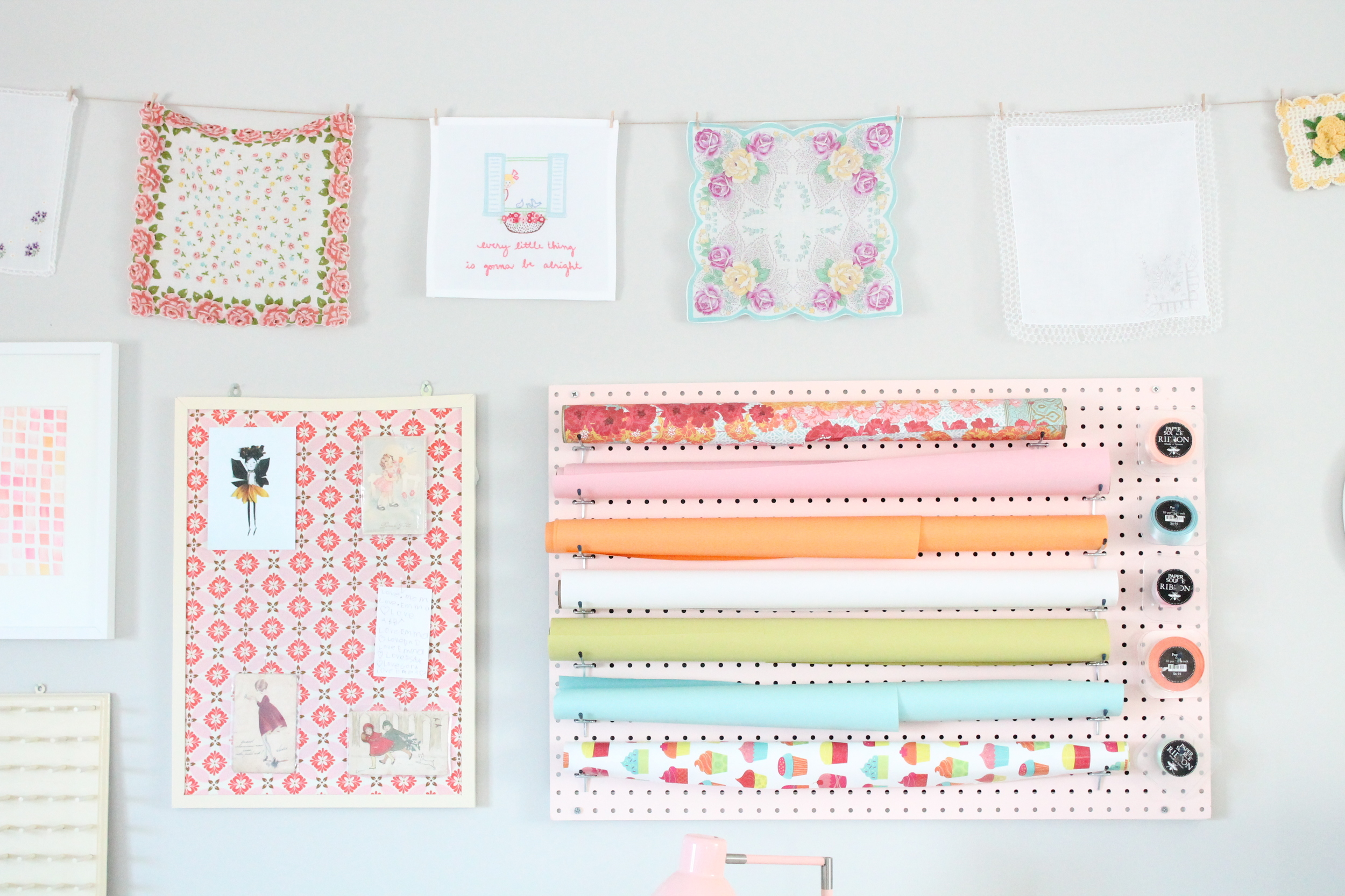 Tessie Fay's family craft room. Pegboard wrapping station, fabric covered bulletin boards and vintage handkerchiefs. So pretty!