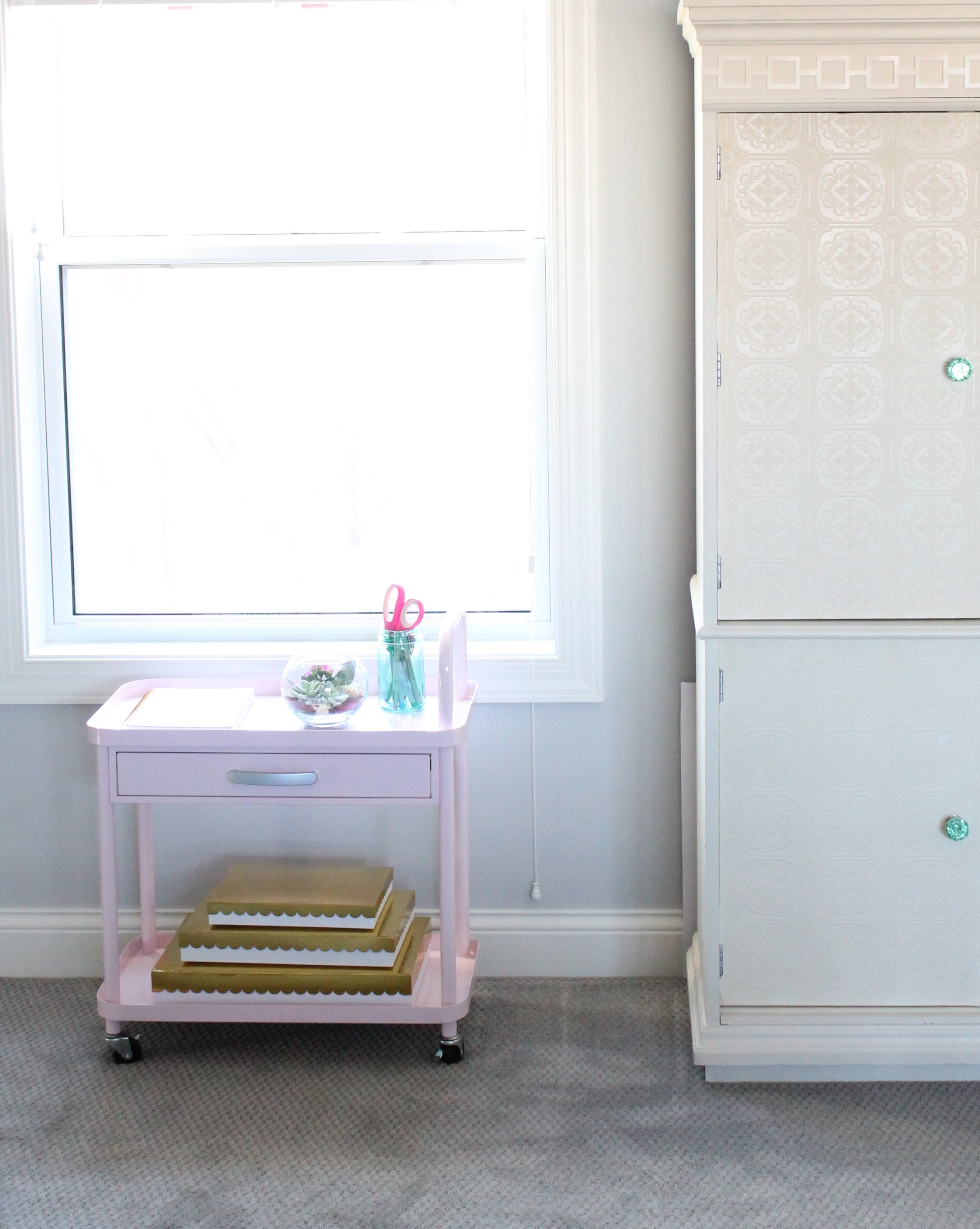 Adorable pink rolling cart in this family craft room.