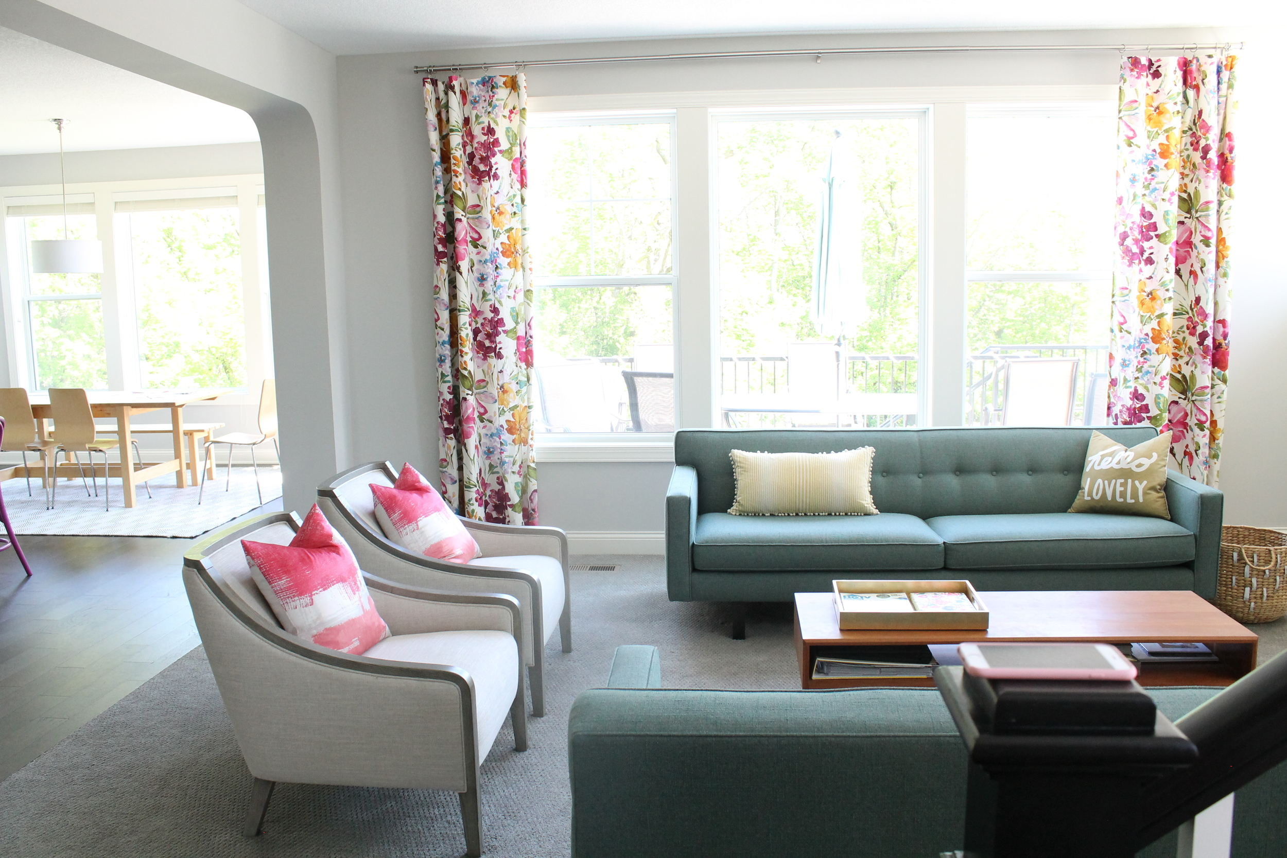 Family Room from Tessie Fay. Love the floral curtains and pops of color.