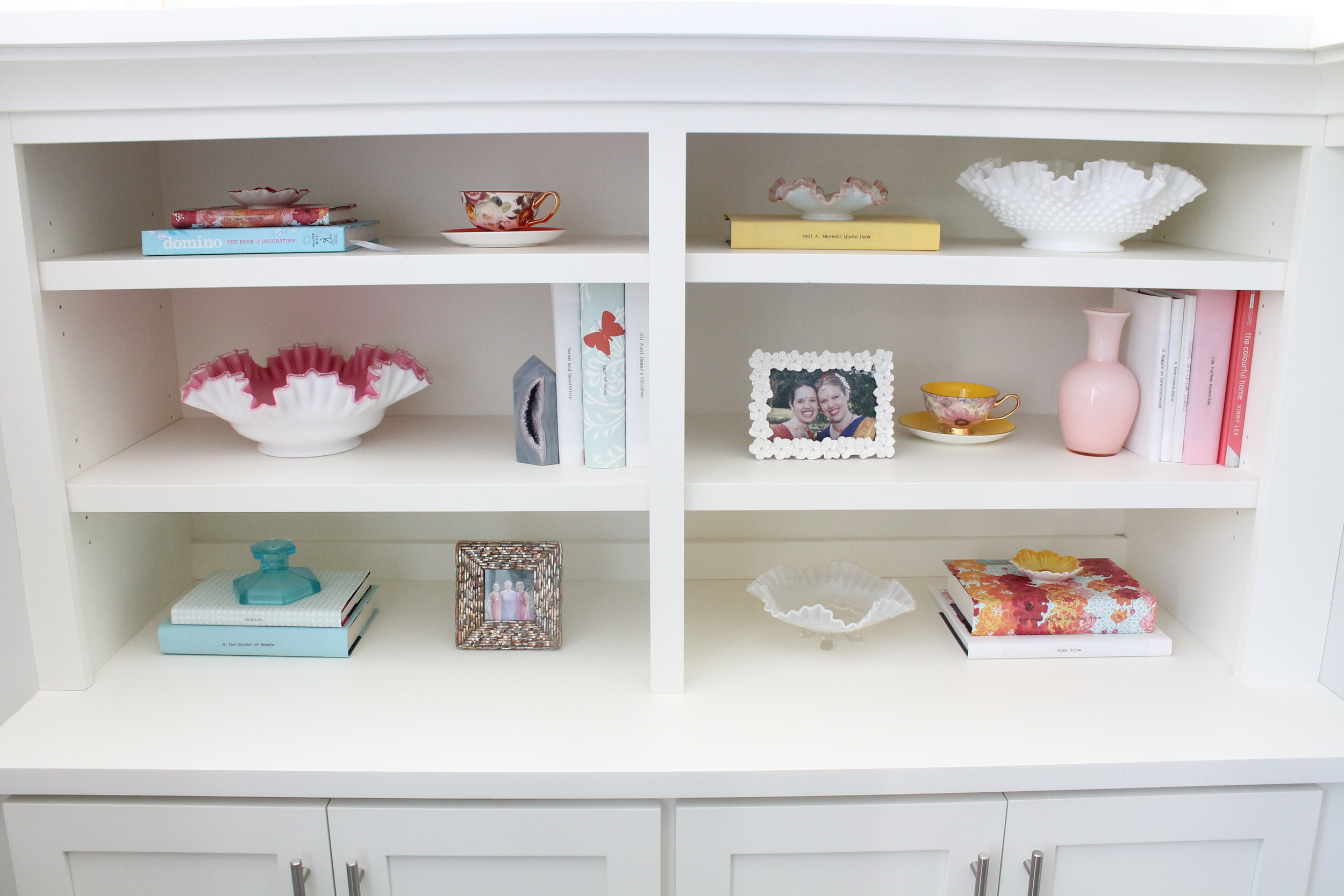 Built in Bookshelf styling with paper covered books and vintage ruffled glass bowls.