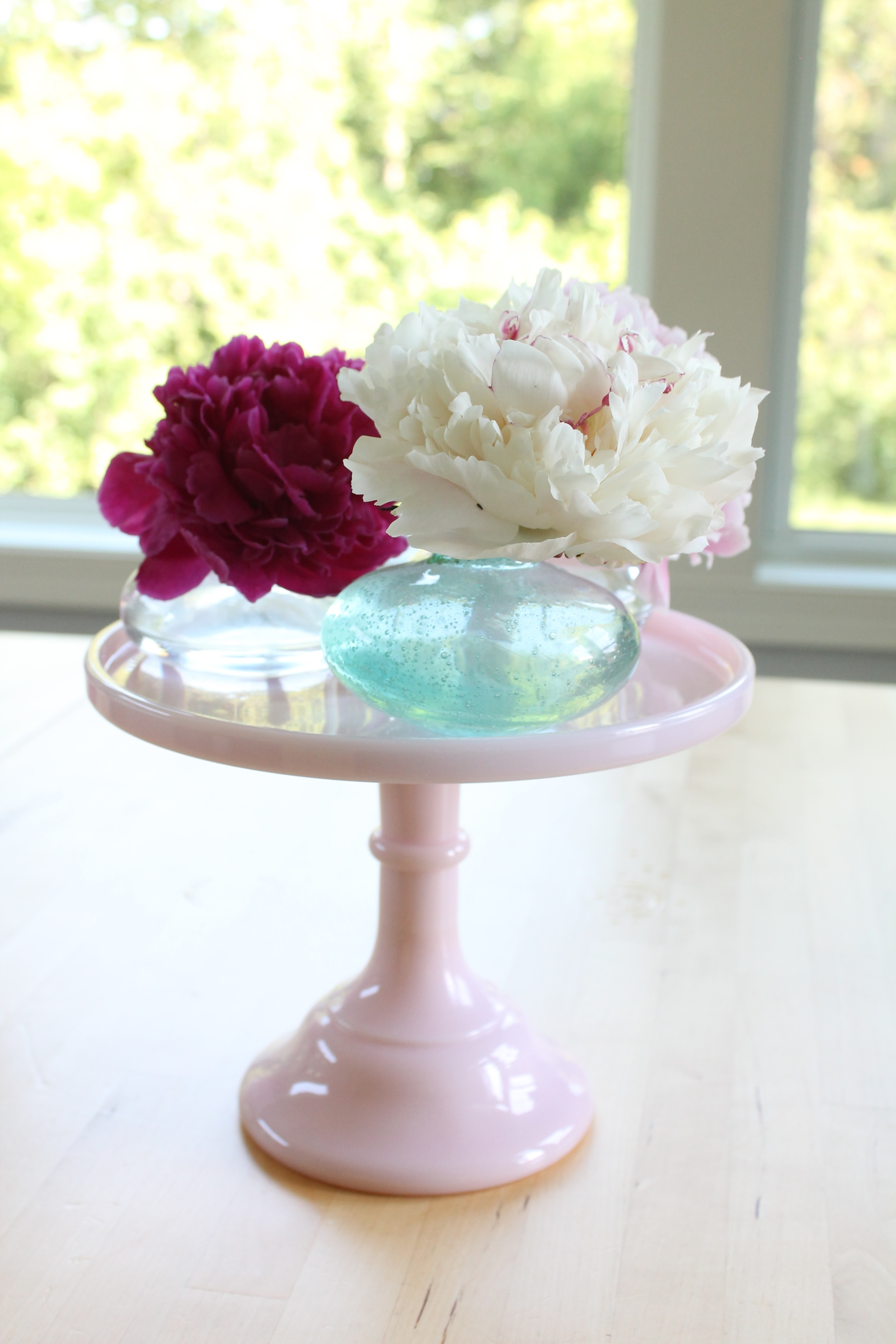 Peonies in bud vases on a pink cake plate.