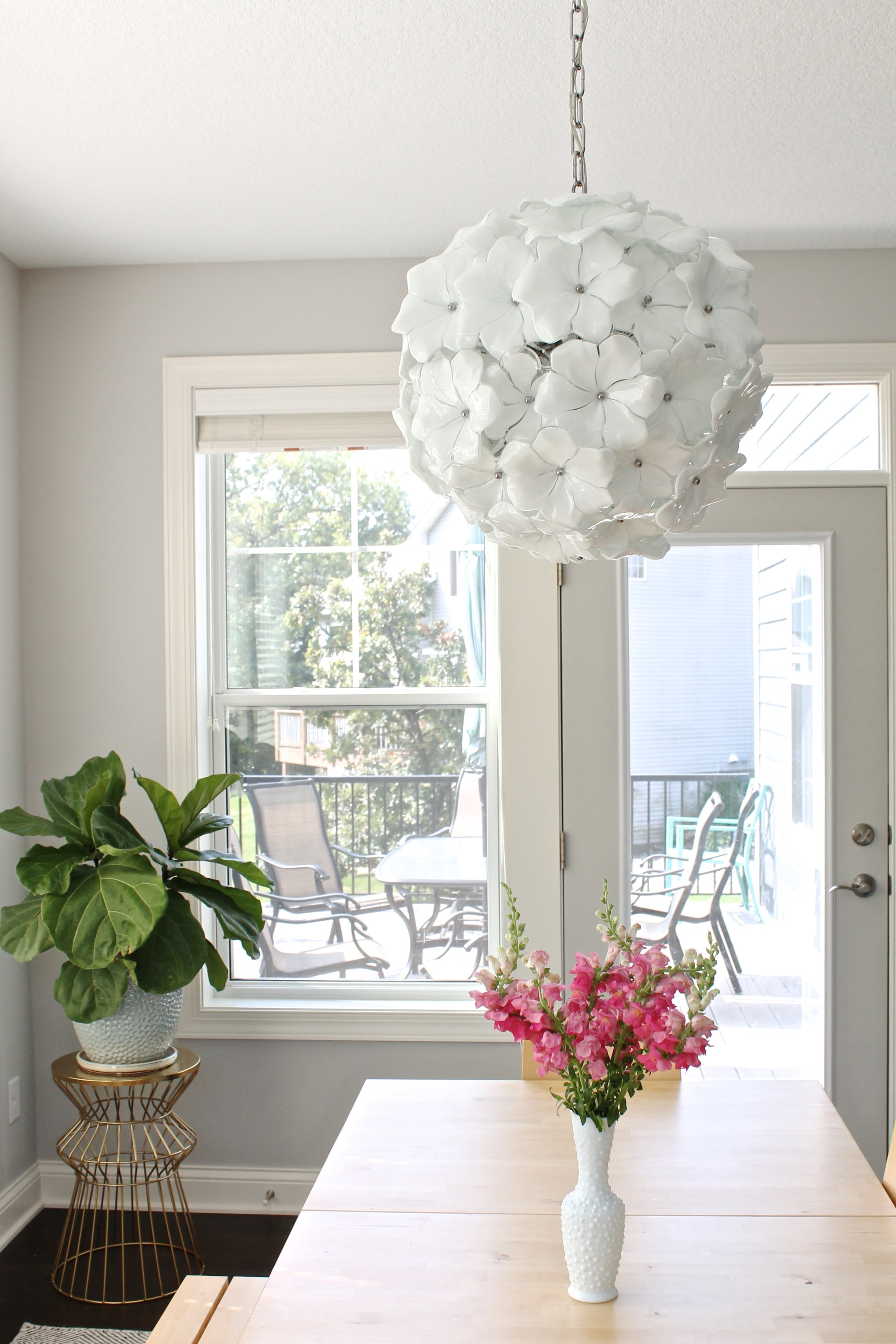 Dining Room with white flower chandelier. Murano glass chandelier. Kitchen table, Fig fiddle leaf and pink snapdragon flowers.