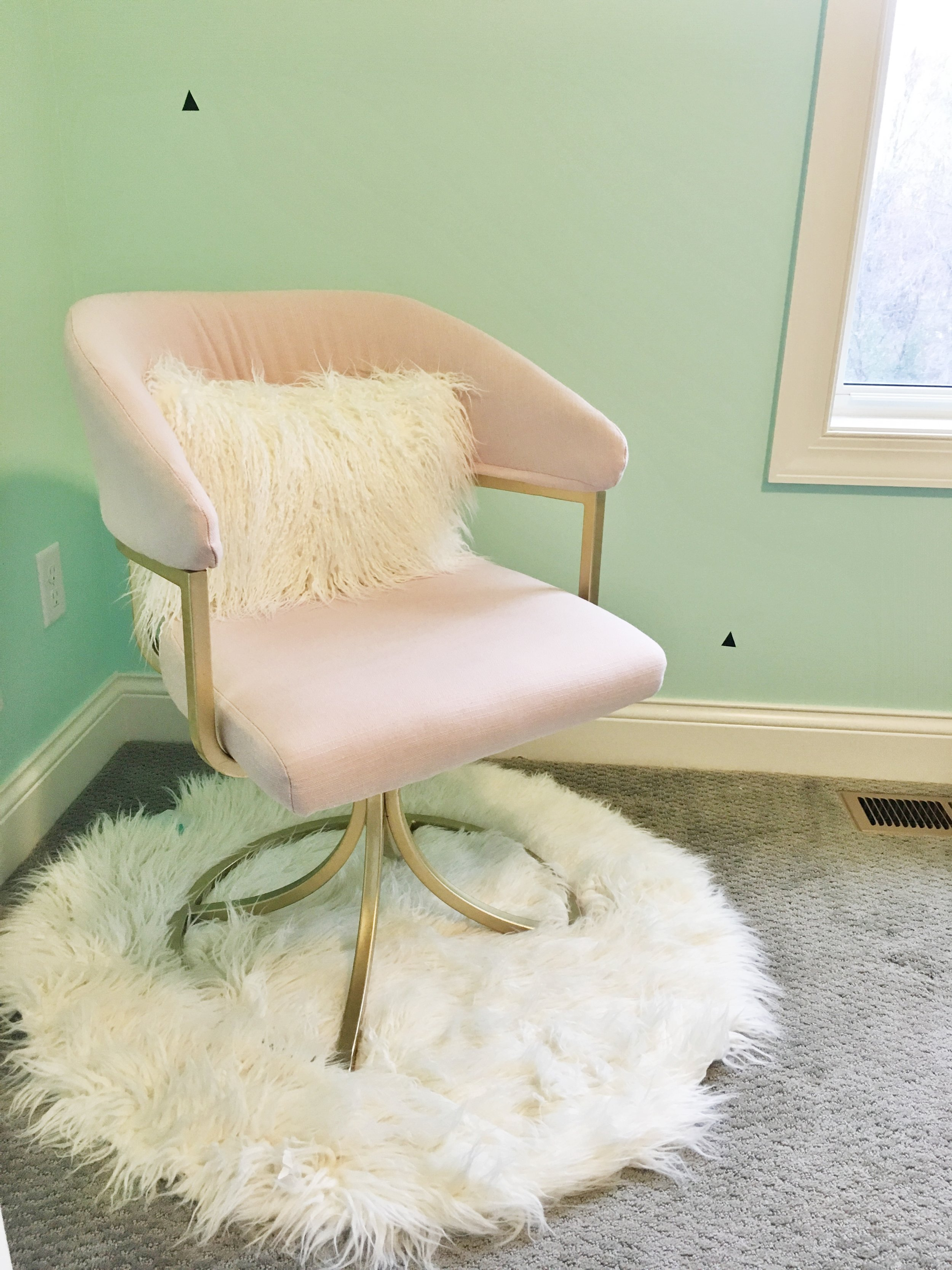 Pink Chair from Home Goods with mint walls and cozy rug