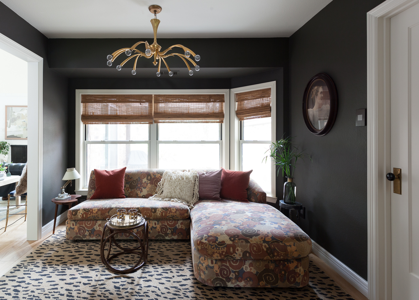 Dark and moody den with pattern on pattern sectional and Metrie door.