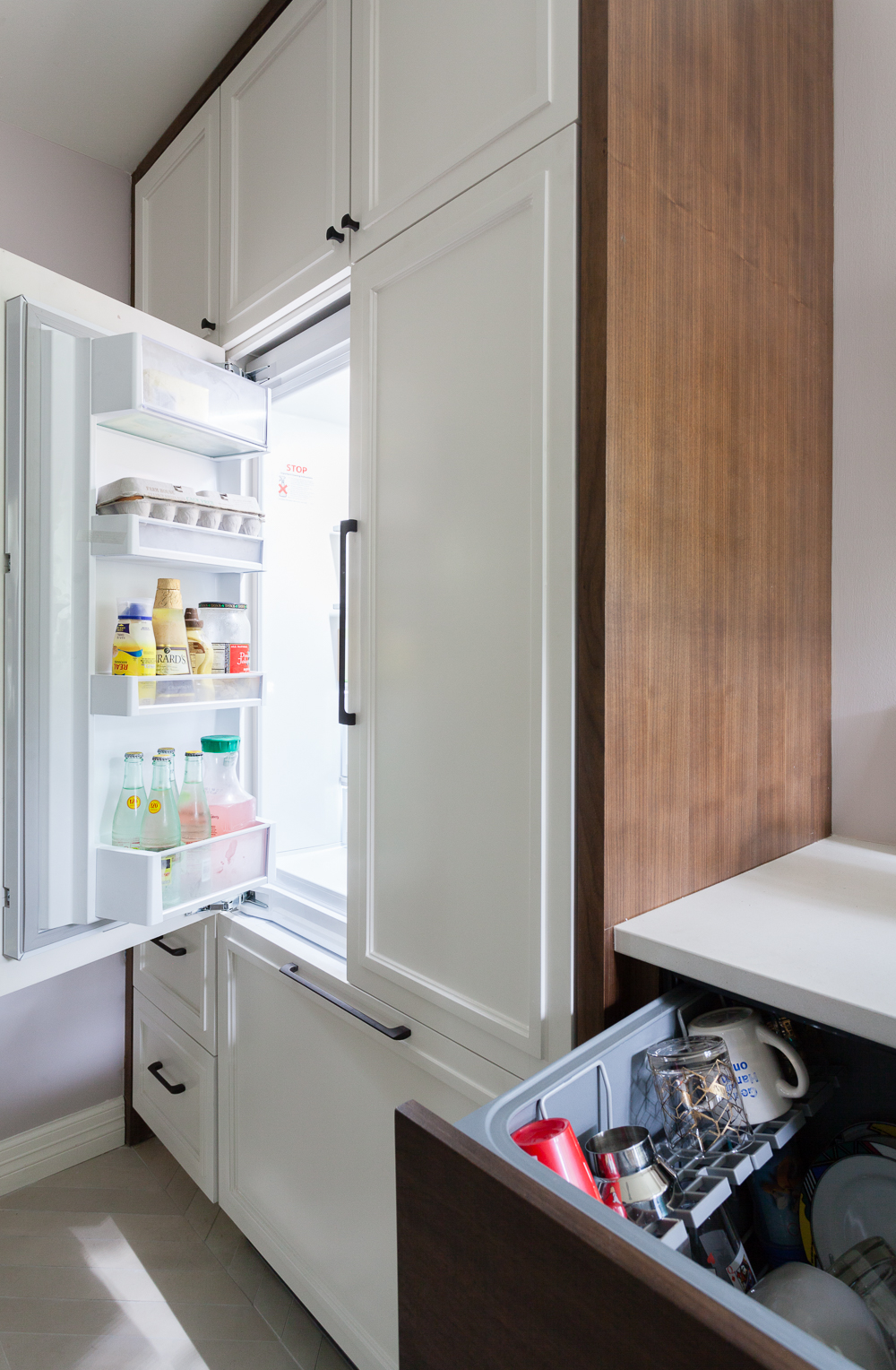 Integrated Fisher and Paykel refrigerator and dishwasher. Custom white cabinets with quartersawn walnut casing.