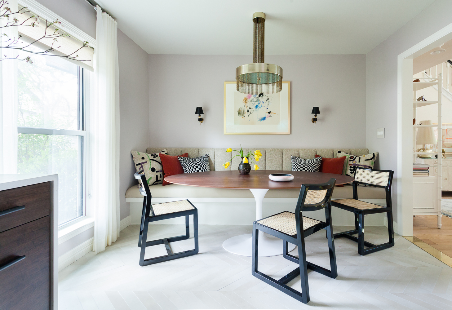 Built in banquette with Saarinen style tulip table with a walnut top vintage Brass fringe Pierre Cardin chandelier and hand sconces. Abstract art by Nancy Lee.