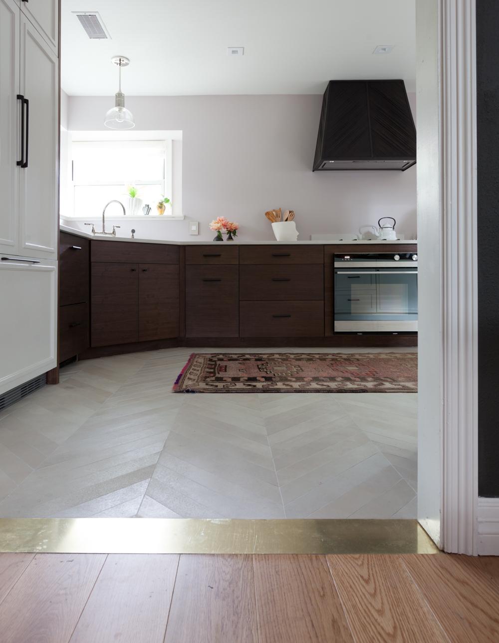 Brass threshold transition strip from white oak wood floors to chevron porcelain floors. Antique vintage Turkish rug.