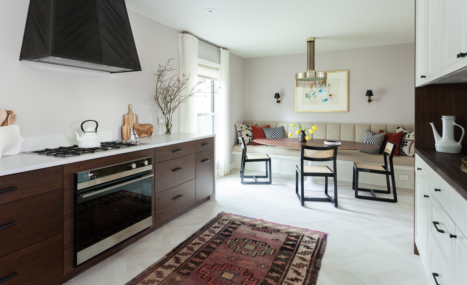Kitchen remodel with chevron floors built in banquette walnut cabinets and modern appliances.