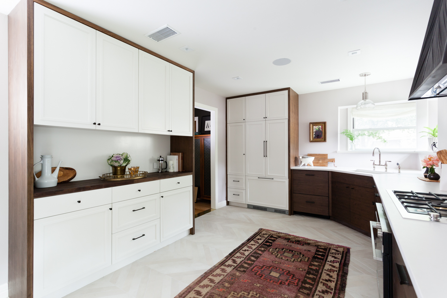 Walnut and white custom cabinets with chevron floors and an integrated refrigerator