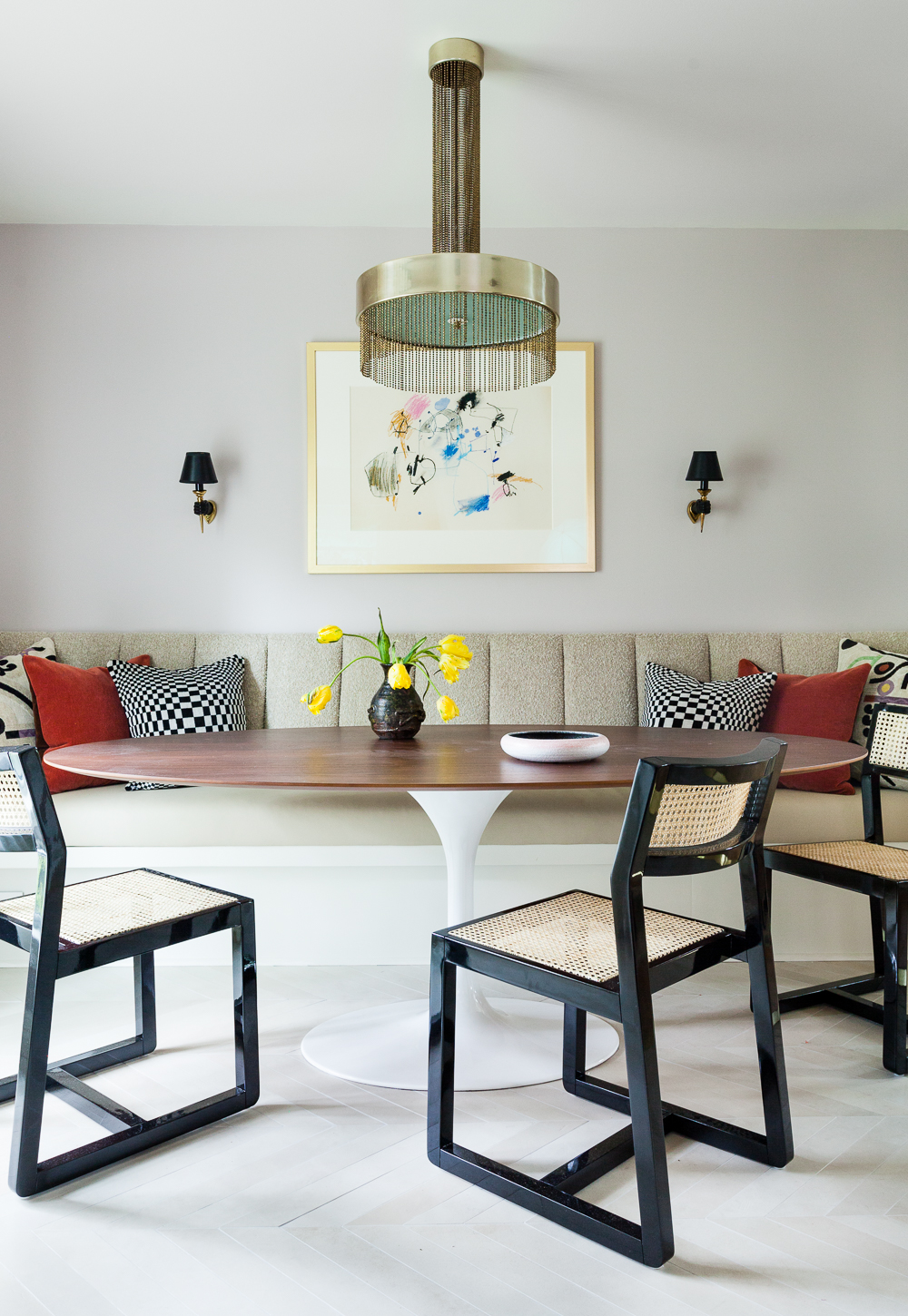 CB2 Makan chairs with walnut tulip table and custom banquette with Fabricut fabric. Vintage brass fringe Pierre Cardin chandelier and art by Nancy Lee. Arbus hand sconces.