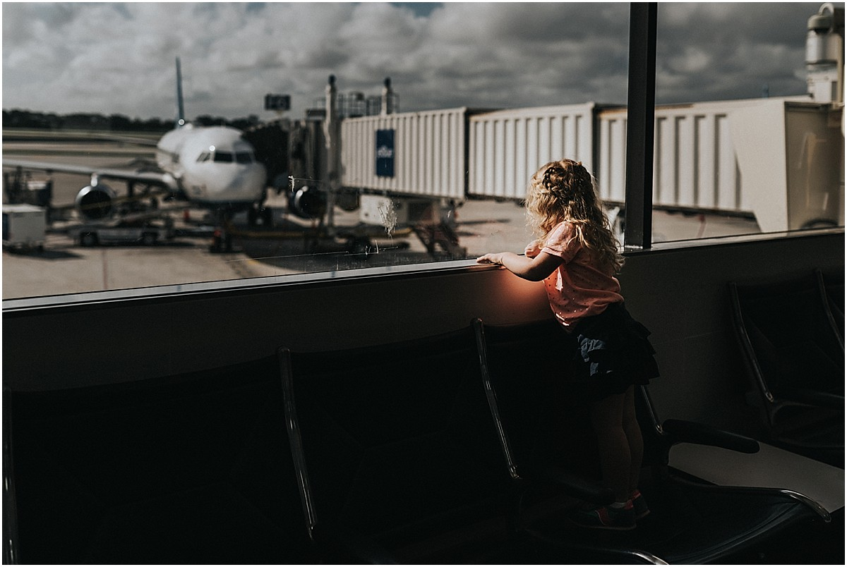 little girl waiting looking at plane at Orlando International Airport