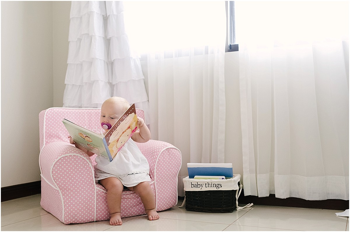 one year old baby girl reading in a chair