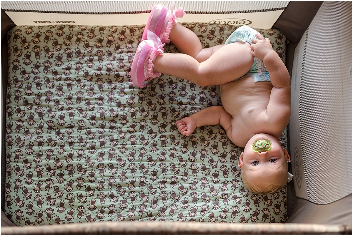 one year old baby in playpen with diaper and pink slippers