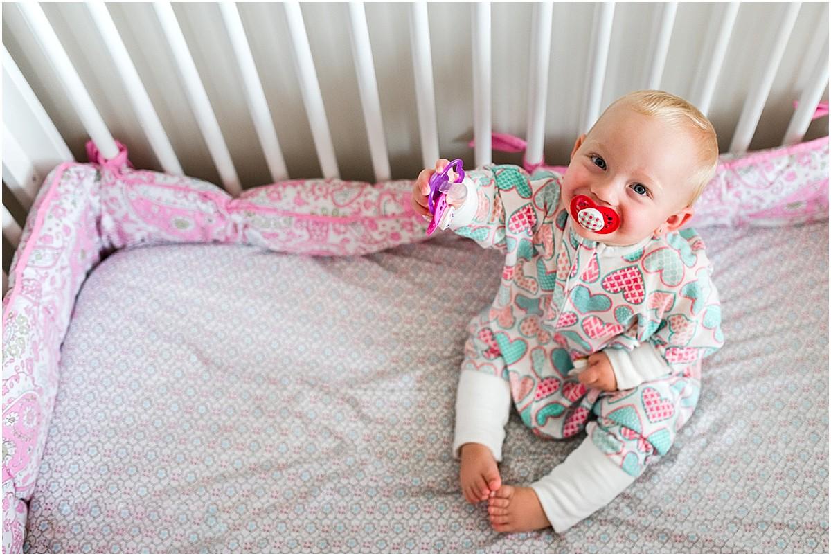 Baby girl in zipadee zip sleep sack with pacifiers in crib