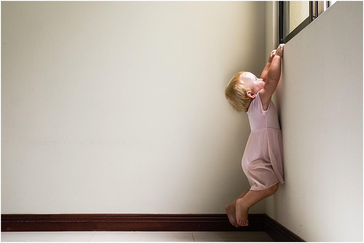 Ballerina baby climbing up a window in Costa Rica house