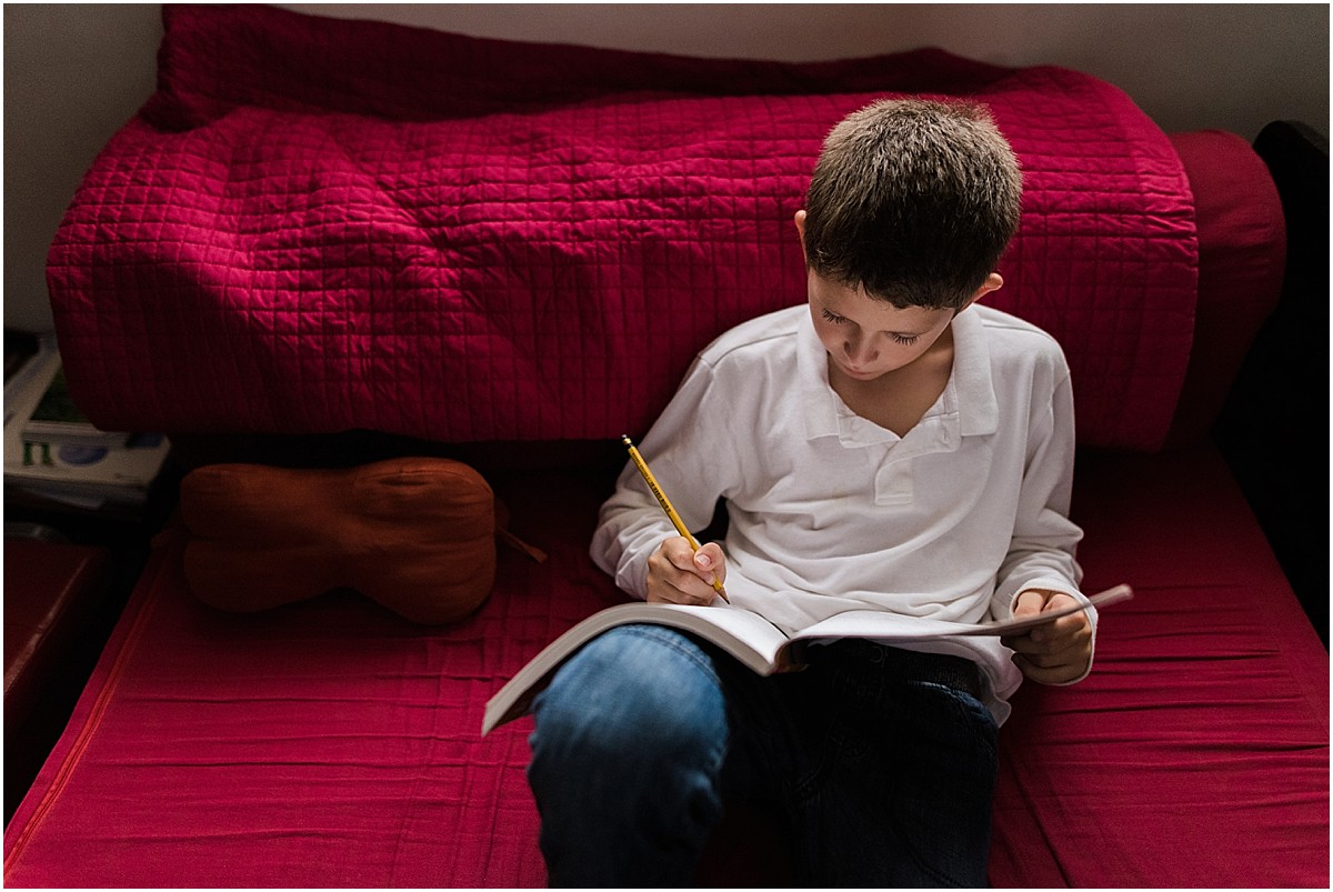 little boy doing homework during lifestyle photoshoot in Costa Rica