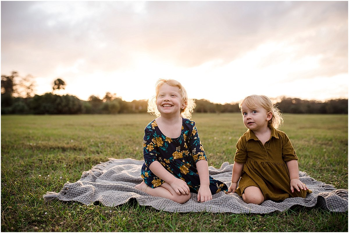 sisters laughing in a field | Orlando Lifestyle Newborn Photographer
