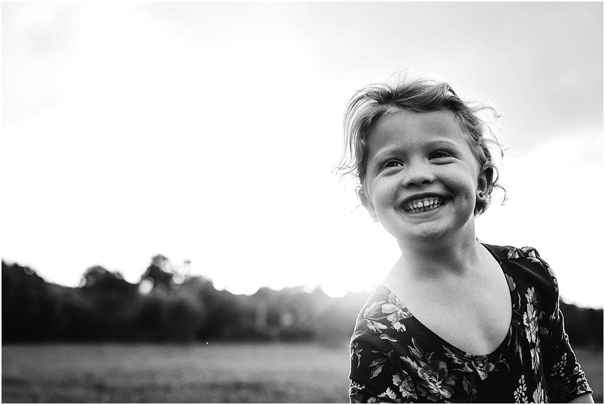 Four year old girl giggling during photoshoot