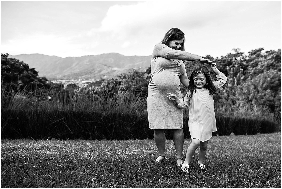 Expecting mother and big sister dancing in a field   Central Florida Maternity Photographer