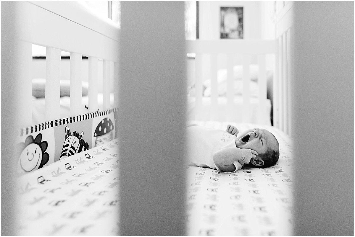 Newborn baby yawning in his crib   Central Florida lifestyle newborn photography
