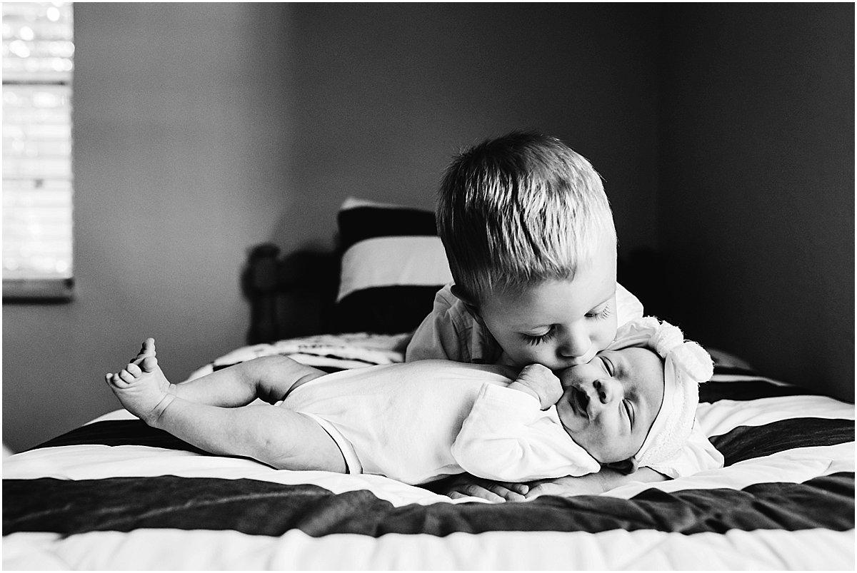 big brother kissing newborn baby sister   Orlando newborn photographer