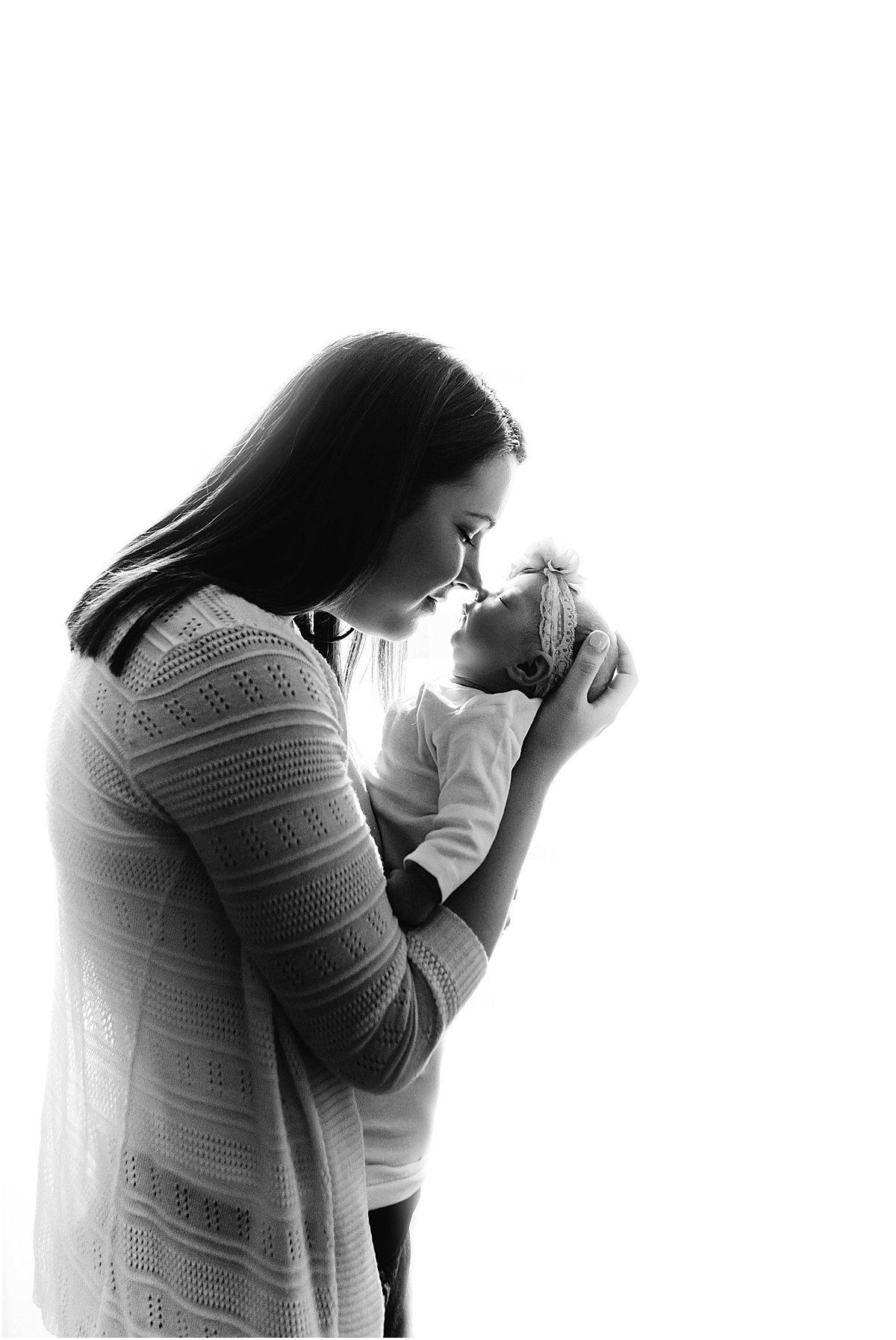 mom kissing newborn baby girl   Orlando lifestyle newborn photographer