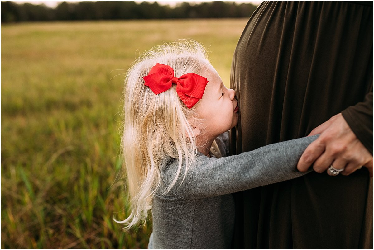 big sister kissing baby brother in mom's belly | Orlando family photographer