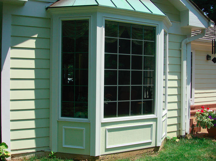 Bay windows with light yellow siding.png