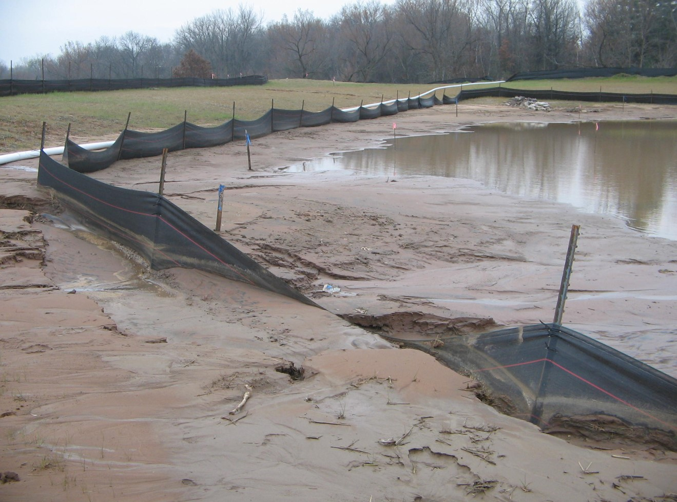 Lower flow rates, improper T-Post spacing, & non-reinforced silt fence fabric combine for a failed install.