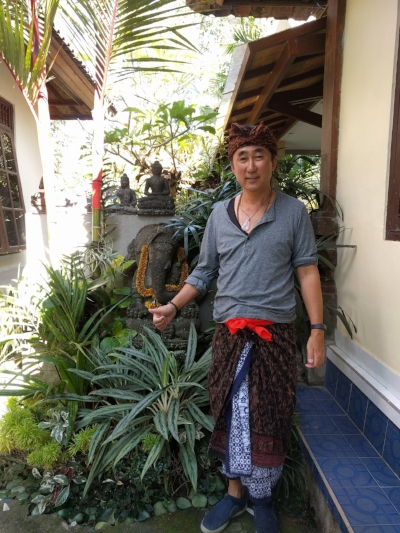 Traditional Balinese  udeng  headdress on top, sarong underneath a  saput  (or outer sarong), tied together with an  anteng  (sash), all courtesy of my host  Cito , plus a Henley shirt from H&M, under shirt from Uniqlo, rose quartz from Luang Prabang, Laos, and shoes from  Fleet Feet!  (I'm about the only person in Bali wearing shoes, by the way. Or it seems that way.)