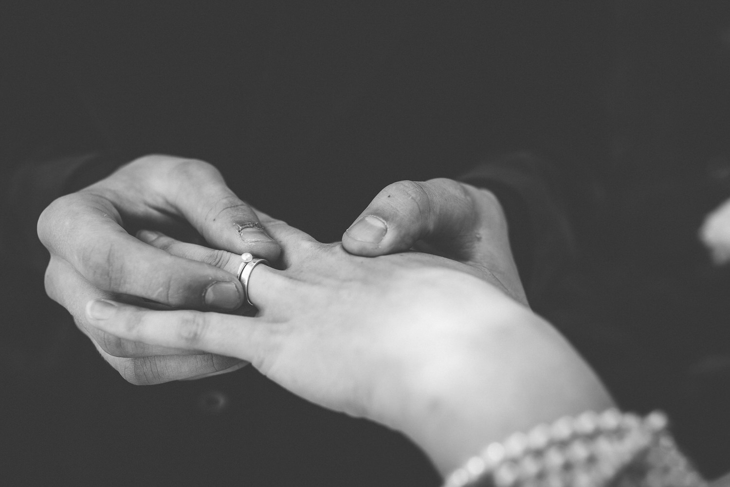 groom putting a ring in bride's finger