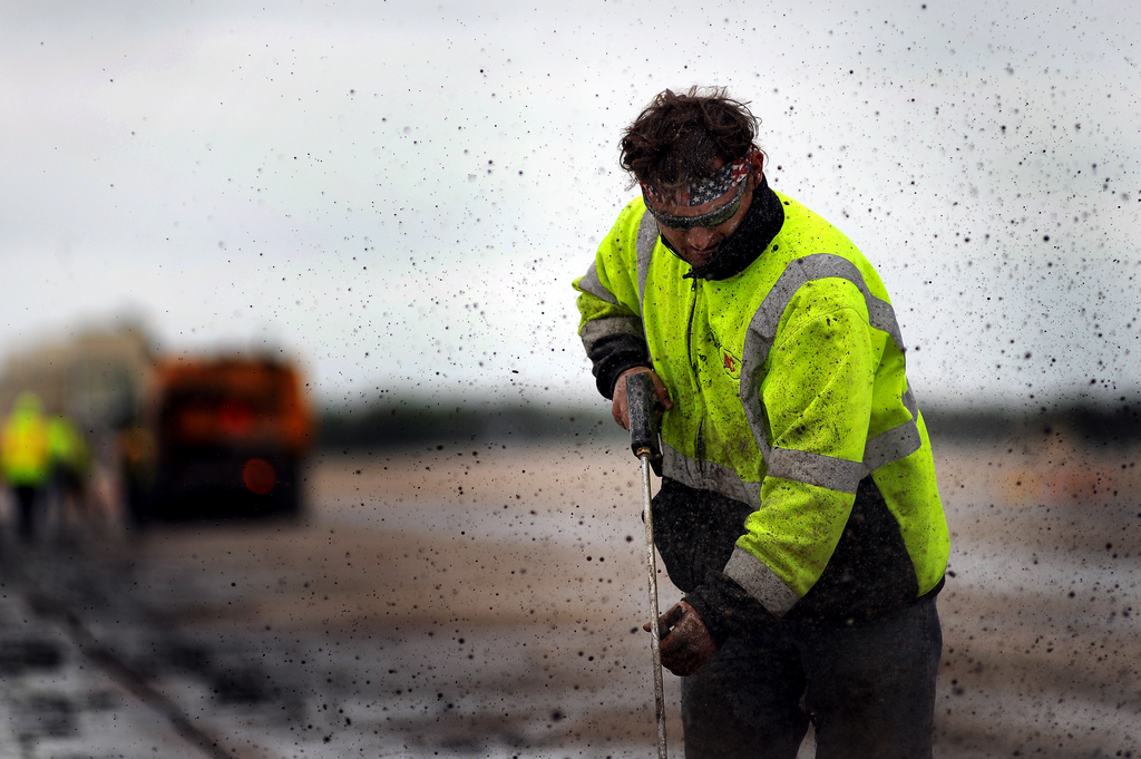 The worker in this image needs to wear a face shield to protect from particles and fragments being blown back by the high pressure tool he is using.
