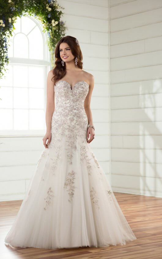 """D2398 - Made for the bride who wants to be a princess on her big day, this sparkling, A-line designer wedding dress by Essense of Australia is magical! Lace and tulle form a sweetheart neckline and frothy skirt, which is richly beaded around the bodice. The beadwork continues down the length of the full skirt and into the long, sweeping princess train. Silver lace plays up the metallic finish and dropped waist. The back of this shimmering princess gown is available in a lace up back, or as an easy close zipper under classic crystal buttons. Also available in plus size, this princess dream dress is perfect for any """"I Do.""""  Colors Available - White/Silver, Ivory/Silver"""