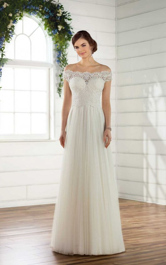 D2446 - An easy, breezy, boho style, this off-the-shoulder wedding dress from Essense of Australia is the perfect addition to your beachside ceremony. Designed in a beautiful cotton lace over French lace pattern, the soft lace bodice of this gown is available lined or unlined and is accented perfectly with scalloped off-the-shoulder sleeves for that truly laidback look. Beginning at the waist, French tulle extends into a soft sheath silhouette, perfect for walking down the aisle in a beachside setting. The scalloped lace from the neckline of this gown extends around the back, highlighting a sheer bodice. The back of this beach wedding dress zips up beneath pearl buttons and is available in plus sizes.  Colors Available - White, Ivory, Ivory/Moscato