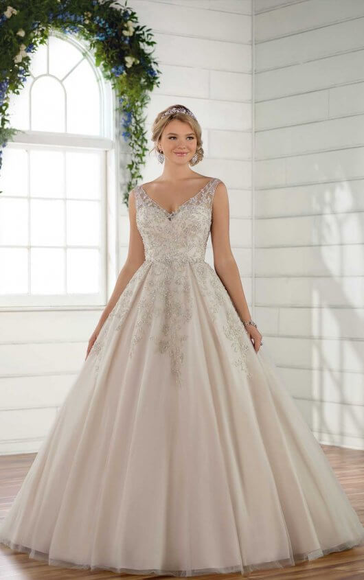 D2499 - Make a statement on your wedding day in this dramatic ballgown from Essense of Australia! Beaded lace adorns the bodice of this gown, adding the perfect amount of sparkle to an already-breathtaking style. A V-neckline highlights your face effortlessly and is balanced out with a full ballgown skirt, complete with beaded lace detailing around the waist. A sheer V-back highlights the back of this ballgown and is complemented with beaded lace that adorns the back of the skirt and edge of the train, creating a dramatic element as you walk down the aisle. The back of this glamorous ballgown zips up beneath fabric-covered buttons and is available in plus sizes  Colors Available - White/Silver, Ivory/Silver, Ivory/Almond/Moscato/Silver