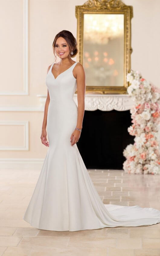 6742 -  Perfect for the bride who craves simple sophistication, this relaxed trumpet wedding dress by Stella York. The matt dove satin fabric slims through the bodice and hips and flares with ease just below the bride's knees, creating an enviable silhouette. Curved seaming on the bodice adds shape and subtle detail to the dress. This high end look comes with a plunging V-neckline and low dipped back which add an element of sexiness to this wedding dress.     Available in - White, Ivory