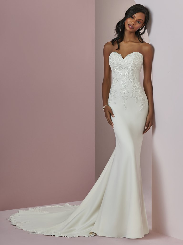 Billie -  This Aldora Crepe fit-and-flare wedding gown features embroidered lace motifs along the bodice, strapless sweetheart neckline, and back hemline. Subtle illusion accented in lace motifs completes the scoop back. Finished with crystal buttons and zipper closure.     Available in - Soft Pearl