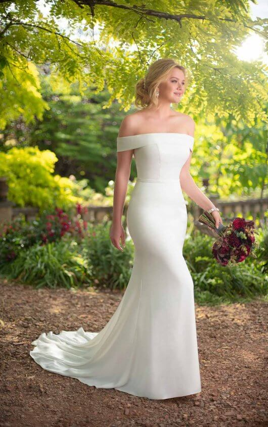 D2717 -  A sexy update to today's royally-inspired style, this simple sheath wedding dress from Essense of Australia will look just as great walking down the aisle as it will dancing the night away! The gown's banded, off-the-shoulder neckline gives the gown a sophisticated look and is accentuated with an attached fabric belt to highlight the waist.    Available in - White, Ivory