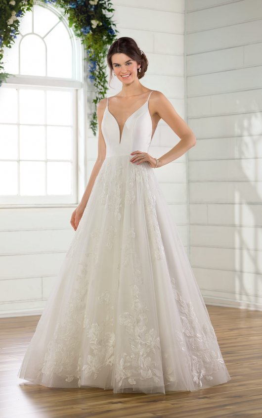 D2810 -  Get ready to turn heads in this chic ballgown with floral tulle skirt! This mixed creation features a Mikado bodice with clean lines and a skinny plunge, complete with shoestring straps for an effortless simplicity. The V-side cutouts mirror the scooped V-back perfectly, showing your skin in an elevated new way. The multi-layer tulle skirt makes a bold statement with a variety of large-scale floral patterns intermingling throughout the gown and against the wide horsehair trim for a structured yet airy hemline. The back of the gown zips beneath four fabric covered buttons at the base of the open back, before flowing out into a short, effortless train for a frothy finish. This wedding dress is also available in plus sizes.    Available in: White, Ivory